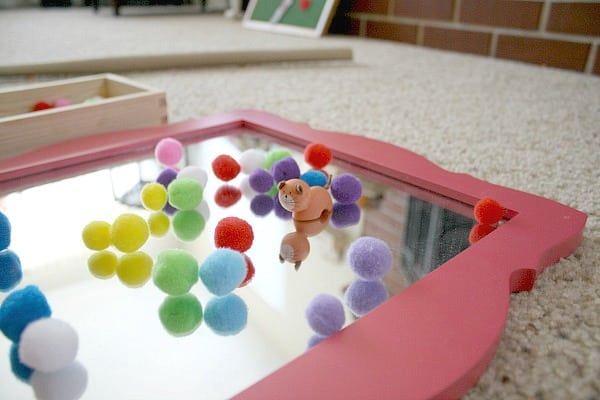 Toddler Activity: Invitation to play with pom poms and a mirror