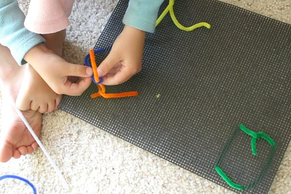 Working on invitation to create with pipe cleaners and plastic canvas