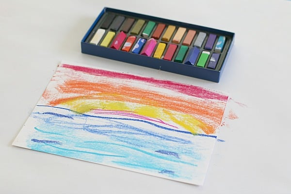 Drawing ocean and sunset scene with chalk