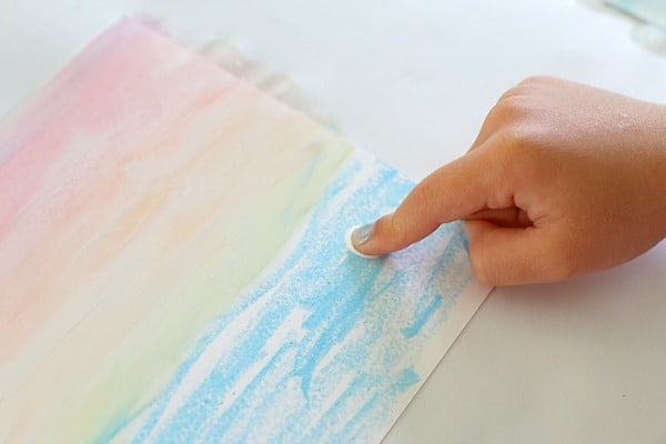 Using finger to paint with tempera and chalk