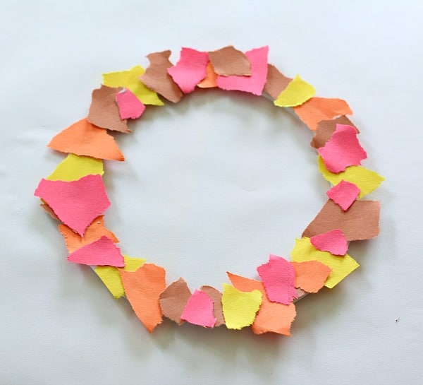 Glue torn pieces of construction paper onto the circle