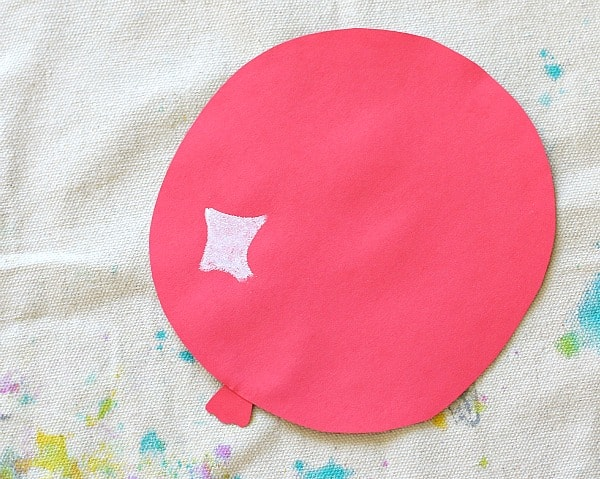 cut out a balloon shape from red construction paper