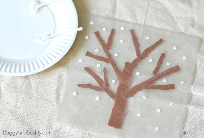 use a q-tip (cotton swab) and tempera paint to make snowflakes on your suncatcher