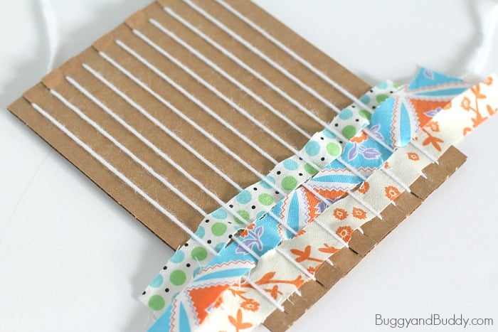 weave fabric strips through the cardboard loom