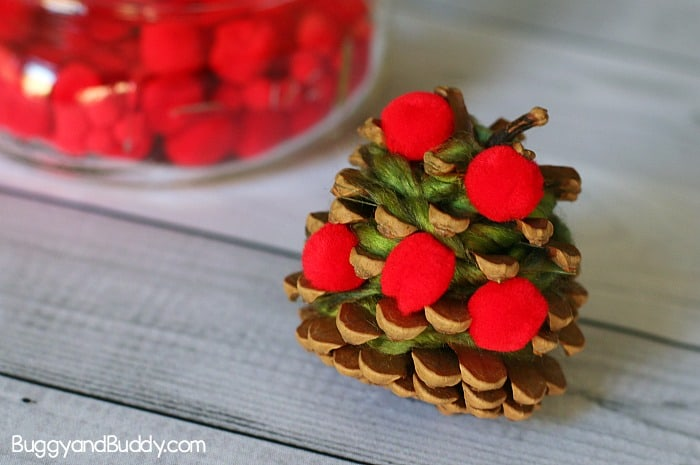 glue red pom poms to your pinecone for the apple tree craft for kids