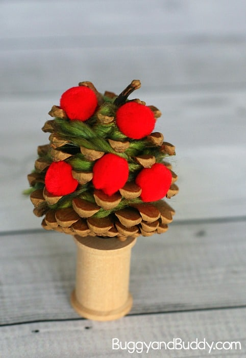 use a wooden craft spool as a trunk for your pinecone apple tree fall art project for kids