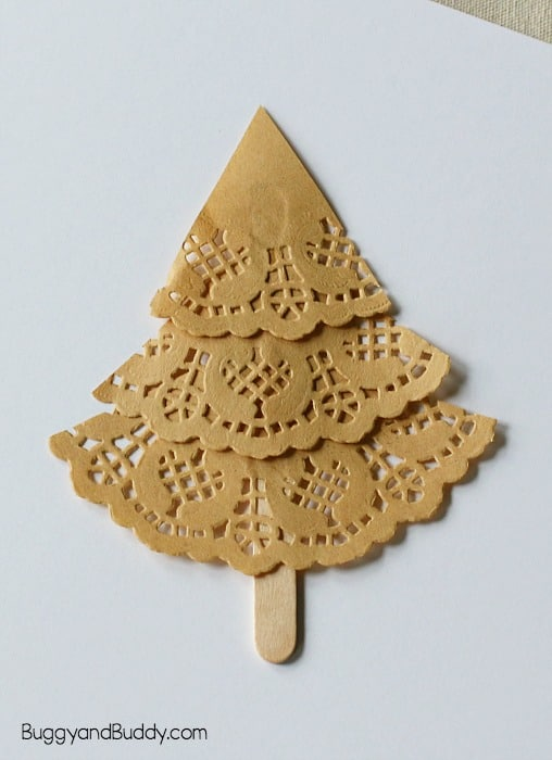 glue your doily pieces onto your popsicle stick to form your christmas tree craft