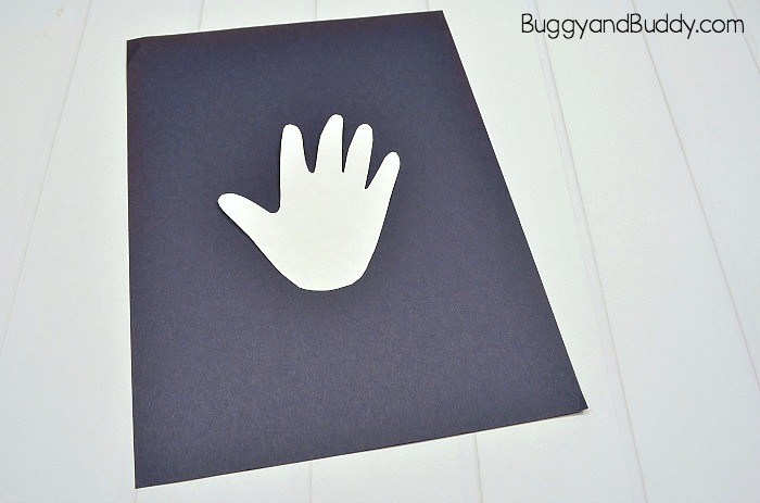 tape your cut out handprint to the black paper