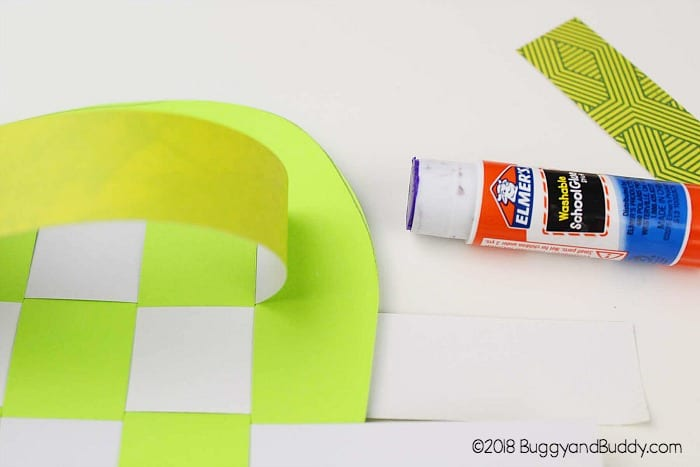 glue the woven paper strips down to your apple shape